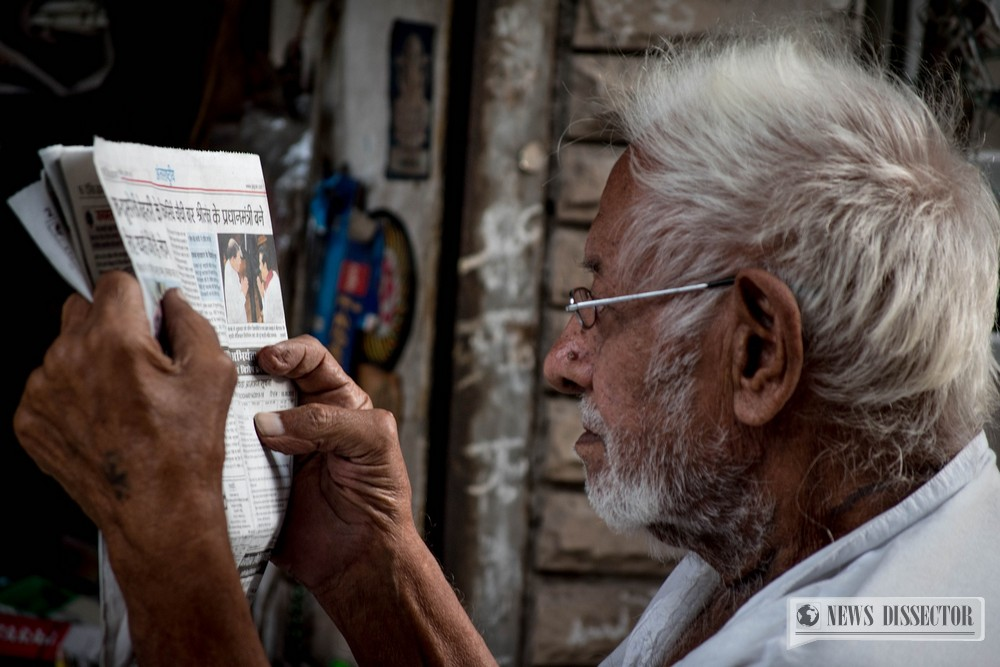 An old man reading an article