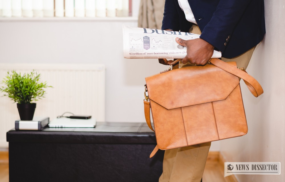 Man carrying a business bag and a newspaper