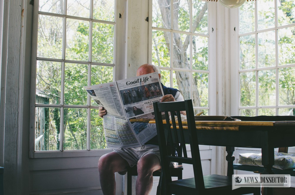 Old man reading a newspaper in his own home