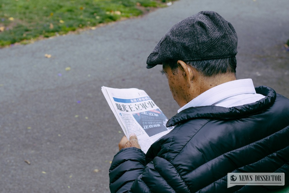 Old man reading a newspaper