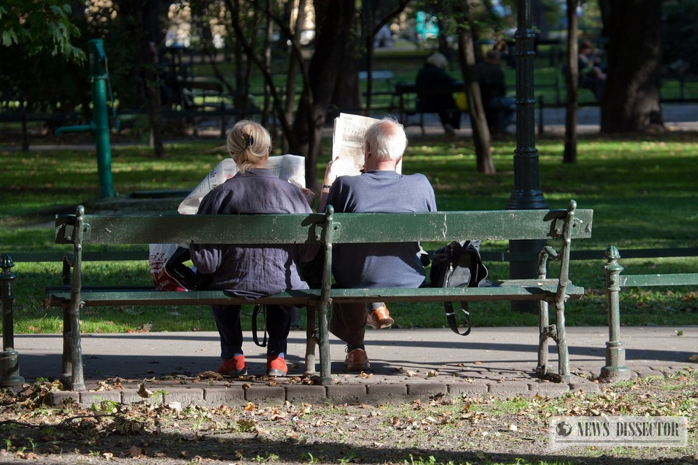 People reading the newspaper on a bench