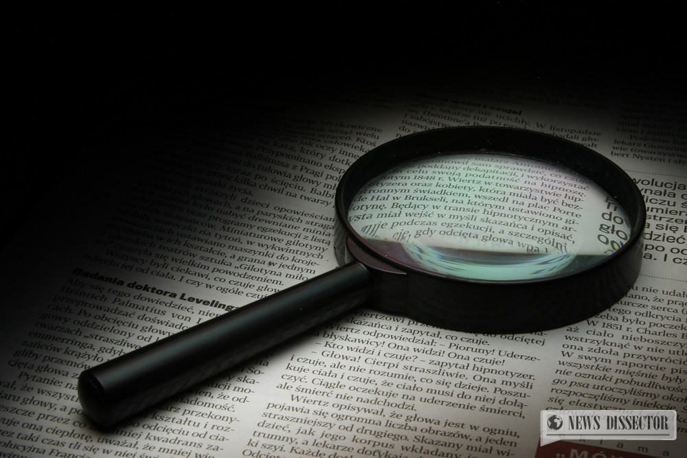 A magnifying glass over a newspaper