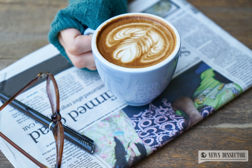 A woman having a relaxing time, reading the paper, drinking some coffee