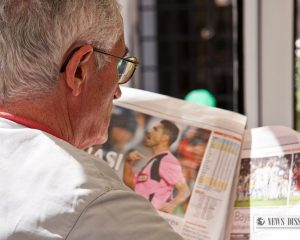 An old man reading the sports section of a tabloid
