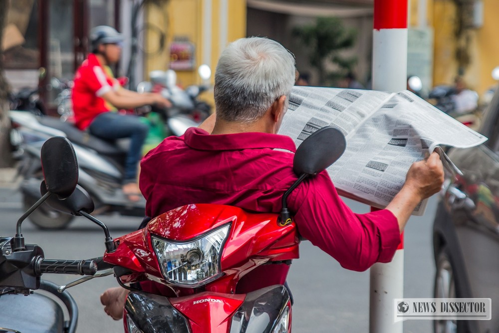 Man reading a newspaper on a scooter